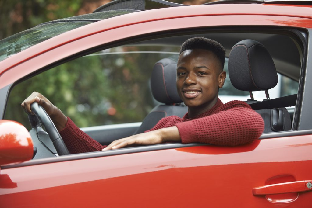 Male Teenage Driver Looking Out Of Car Window