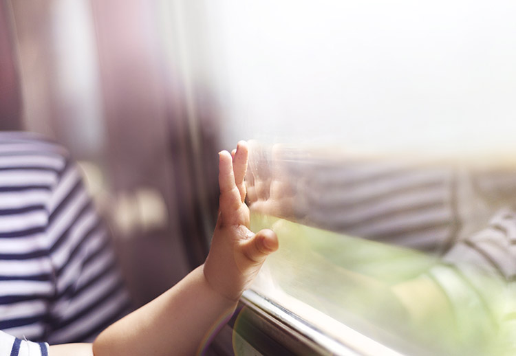 Photo of a boy travelling and touching the window.