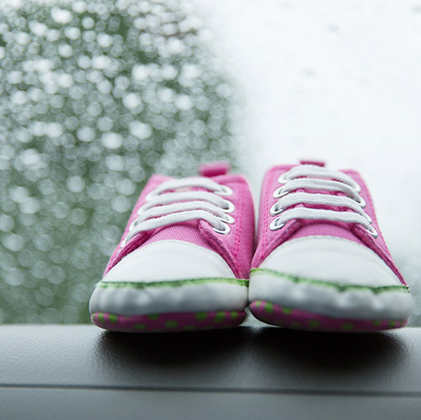 Photo - Pink toddler shoes on a car's dashboard